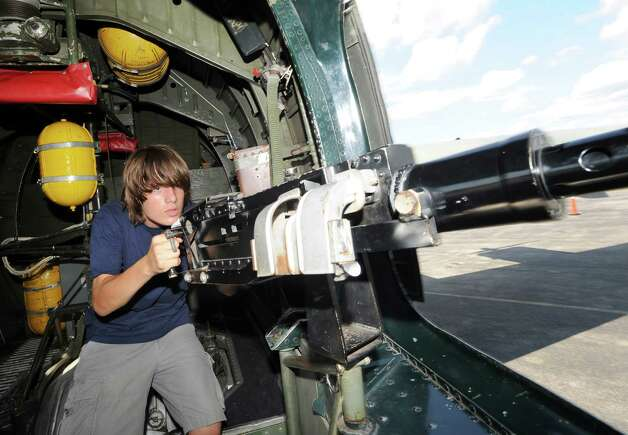 Cris Fitzgerald, 14, of Old Greenwich, handles a .50-caliber machine gun inside a B-24 Liberator bomber during the annual World War II plane traveling exhibition, Wings of Freedom tour, at Westchester County Airport in White Plains, N.Y., Tuesday, Aug. 21, 2012. The aircraft will be on display and available for paid flights from 9 a.m. to noon Aug. 22, before leaving the airport. Photo: Bob Luckey / Greenwich Time