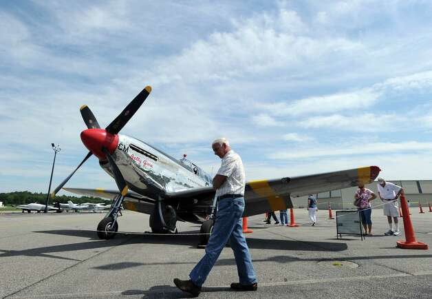 Michael Mancuso of Mahopac, N.Y., walks past a P-51 Mustang fighter during the annual World War II plane traveling exhibition, Wings of Freedom tour, at Westchester County Airport in White Plains, N.Y., Tuesday, Aug. 21, 2012. The aircraft will be on display and available for paid flights from 9 a.m. to noon Aug. 22, before leaving the airport. Photo: Bob Luckey / Greenwich Time