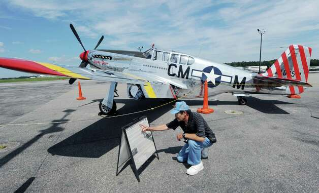Mel Zane of Haverstraw, N.Y., reads the information about the P-51 Mustang fighter, background, during the annual World War II plane traveling exhibition, Wings of Freedom tour, at Westchester County Airport in White Plains, N.Y., Tuesday, Aug. 21, 2012. The aircraft will be on display and available for paid flights from 9 a.m. to noon Aug. 22, before leaving the airport. Photo: Bob Luckey / Greenwich Time