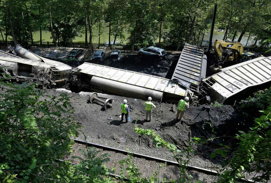 A CSX freight hauling coal from West Virginia derailed around midnight Monday derailed and fell from a bridge near Baltimore, killing two college students on the bridge. Their bodies were found buried under coal. Photo: Patrick Semansky / AP