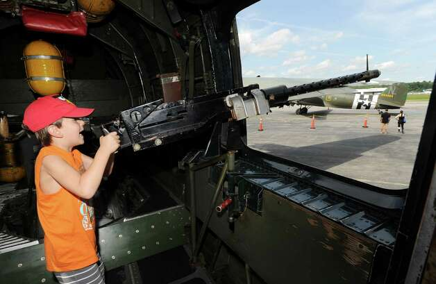 Michael Caldropoli, 6, of Yonkers, N.Y., plays with the 50 caliber machine inside the B-24 Liberator bomber during the annual World War II plane traveling exhibition, Wings of Freedom tour, at Westchester County Airport in White Plains, N.Y., Tuesday, Aug. 21, 2012. Photo: Bob Luckey / Greenwich Time