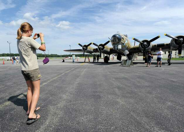 Ellie Fitzgerald, 12, of Old Greenwich, takes a photo of a B-17 Flying Fortress bomber during the annual World War II plane traveling exhibition, Wings of Freedom tour, at Westchester County Airport in White Plains, N.Y., Tuesday, Aug. 21, 2012. The aircraft will be on display and available for paid flights from 9 a.m. to noon Aug. 22, before leaving the airport. Photo: Bob Luckey / Greenwich Time