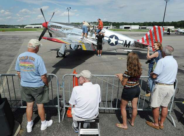 Spectators get a look at a P-51 Mustang fighter during the annual World War II plane traveling exhibition, Wings of Freedom tour, at Westchester County Airport in White Plains, N.Y., Tuesday, Aug. 21, 2012. Photo: Bob Luckey / Greenwich Time