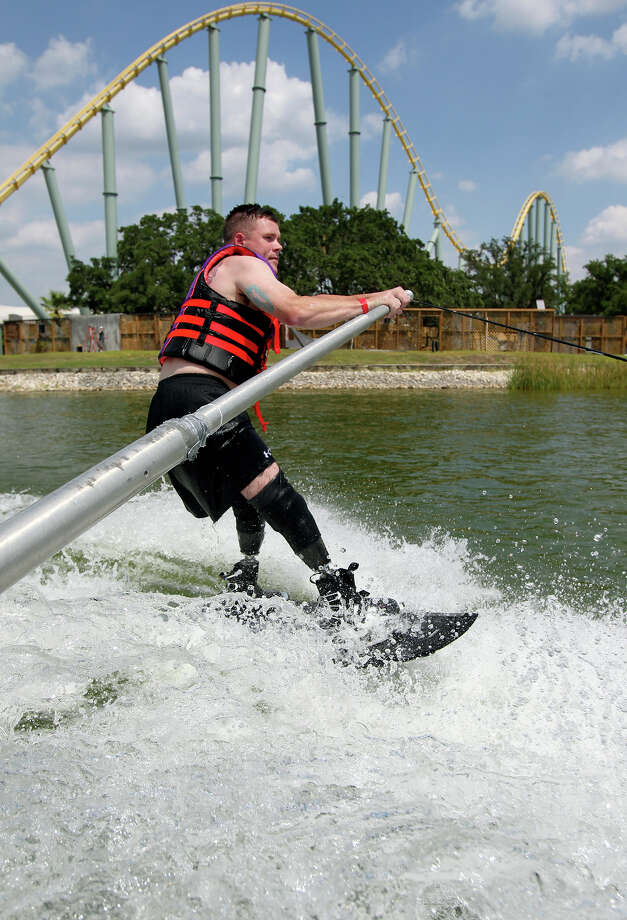 Jason Rzepa cruises under the roller coaster track on a ski run as volunteers help with All Can Ski, a waterskiing clinic for people with disabilities, at SeaWorld on August 21, 2012.  Rzepa lost his lower legs when an IED detonated in Iraq in 2011.  (He emphasizes that it happened in Iraq.) Photo: Tom Reel, San Antonio Express-News / ©2012 San Antono Express-News