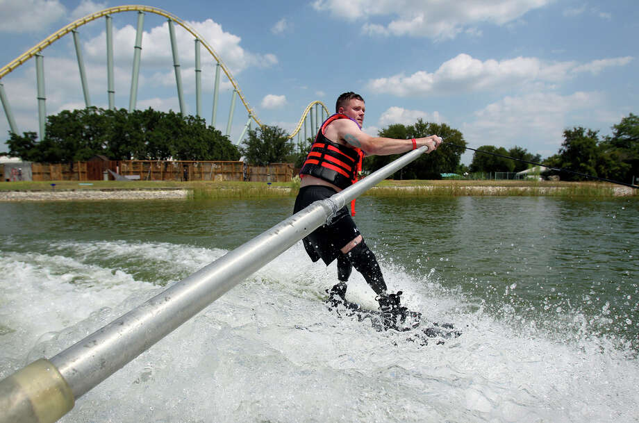 """All Can Ski,"" a waterskiing clinic for people with physical disabilities that's sponsored by San Antonio Sports, is celebrating its 20th anniversary. Tuesday's event on the ski lake at SeaWorld included wounded military men and women, many of whom are being treated at the Center for the Intrepid.Jason Rzepa cruises under the roller coaster track on a ski run as volunteers help with All Can Ski at SeaWorld. Photo: Tom Reel, San Antonio Express-News / ©2012 San Antono Express-News"