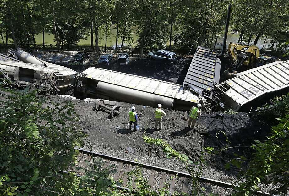 Officials inspect part of a CSX freight train that derailed alongside a parking lot overnight in Ellicott City, Md., Tuesday, Aug. 21, 2012. Authorities say the train, hauling coal from West Virginia to Maryland, derailed and fell from a bridge near Baltimore, killing two college students who were on the tracks. Howard County officials say 21 of the train's 80 cars flipped over around midnight Monday.  (AP Photo/Patrick Semansky) Photo: Patrick Semansky, Associated Press