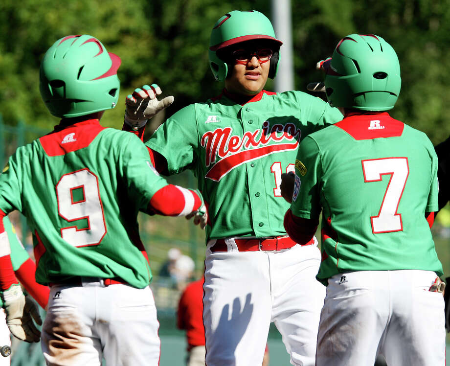 Nuevo Laredo teammates Joel Turrubiates, left, and Fernando Benavides, right, wait for Ramon Ballina after hitting a two-run homerun against Curacao in a must win at the 2012 Little League World Series in South Williamsport, Pennsylvania, Tuesday, Aug. 21, 2012. Nuevo Laredo won 6-2. Photo: Jerry Lara, San Antonio Express-News / © 2012 San Antonio Express-News