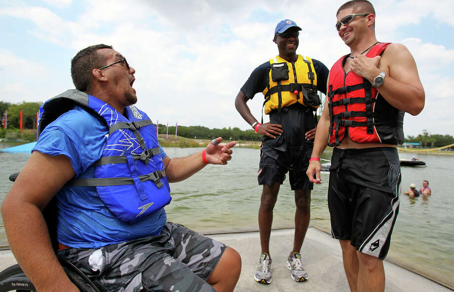 Veteran Sean Michaud (left) shares a laugh with volunteers Terrence Lowe (middle) and Hunter Arnold as they help with All Can Ski, a waterskiing clinic for people with disabilities, at SeaWorld on August 21, 2012. Photo: Tom Reel, San Antonio Express-News / ©2012 San Antono Express-News
