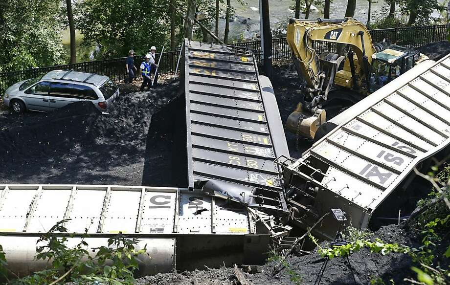 Officials, top left, inspect part of a CSX freight train that derailed alongside a parking lot overnight in Ellicott City, Md., Tuesday, Aug. 21, 2012.  Authorities say the train, hauling coal from West Virginia to Maryland, derailed and fell from a bridge near Baltimore, killing two college students who were on the tracks. Howard County officials say 21 of the train's 80 cars flipped over around midnight Monday.  Photo: Patrick Semansky, Associated Press