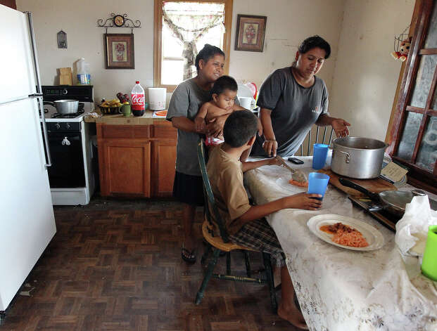 In Hidalgo County, Sonia Garcia, 33 (right), serves lunch to her family in the North San Carlos Colonia. She and her husband have five U.S.-born children and receive $739 in benefits each month. Photo: Kin Man Hui, San Antonio Express-News / ©2012 San Antonio Express-News