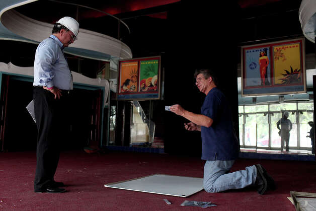 Ernest Bromley (left), chairman of the Alameda Theater nonprofit, works with Robert Herzik, the art director for Bromley's company, on the display of movie posters for the theater. Photo: Lisa Krantz, San Antonio Express-News / San Antonio Express-News