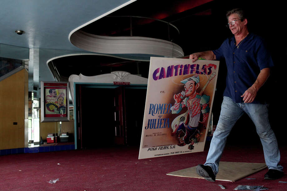 Robert Herzik,  the art director  at Bromley, carries a reproduction of a movie poster to be displayed  in front of the Alameda Theater. Photo: Lisa Krantz, San Antonio Express-News / San Antonio Express-News