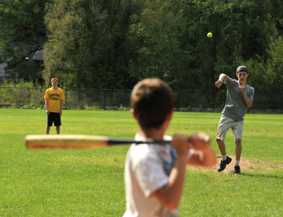 Fielder Austin Bliss-Martinez, 14, left, waits as Nicolas Grosse, 11, attempts to hit the ball being pitched by John Darrah, 15, during a pickup game between cousins at Parloa Park in Bethel on Tuesday, Aug. 21, 2012. Photo: Jason Rearick / The News-Times