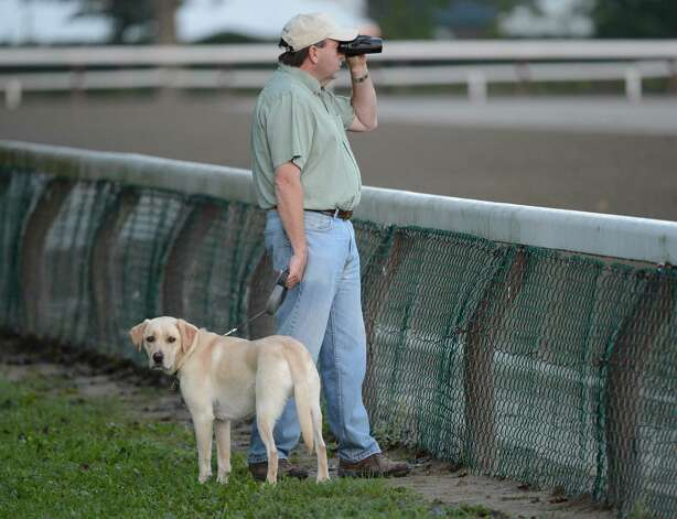 "Trainer Jim Bond with his constant companion ""Charlie"" looks out over the main track for his trainees at the Saratoga Race Course in Saratoga Springs, N.Y. Aug 21, 2012.   (Skip Dickstein/Times Union) Photo: Skip Dickstein"
