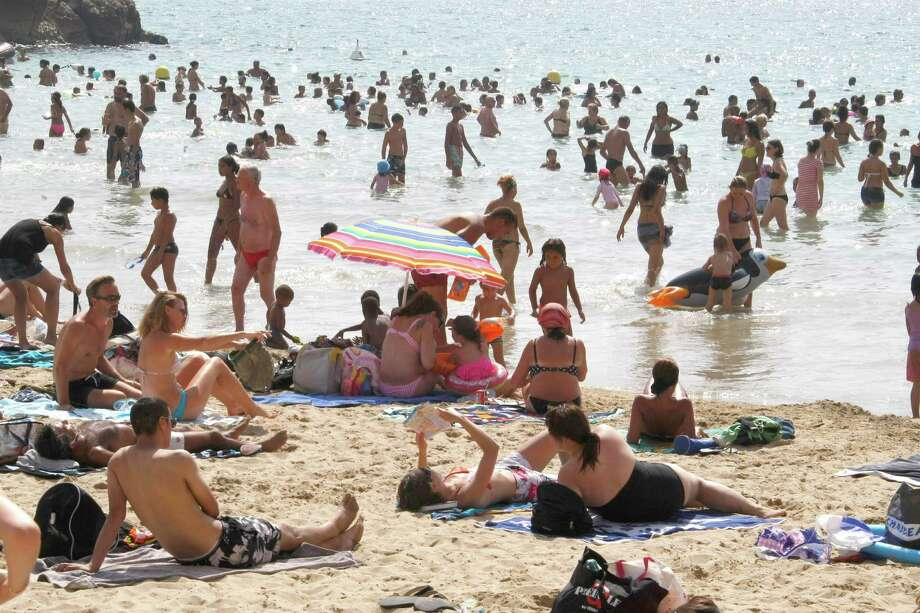 People bathe at the Catalans  beach in Marseille, southern France, Tuesday, Aug. 21, 2012. (AP Photo/Claude Paris) Photo: Claude Paris