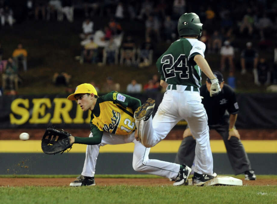 New England's #24 Will Lucas lands at first as West's #12 Danny Marzo attempts the tag out, during 2012 Little League World Series game action in South Williamsport, Penn. on Tuesday August 21, 2012. Lucas was called out but after a review of the play it was reversed. West beat New England 5-0. Photo: Christian Abraham / Connecticut Post