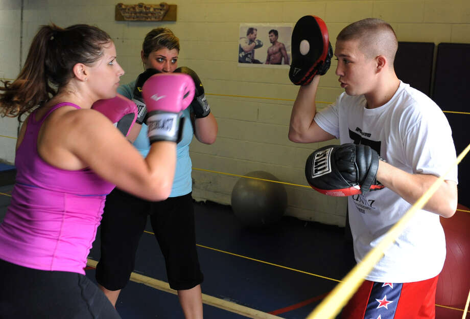 From left, Melissa Terrille, 24, of Latham and Shelby Coons, 25, of Colonie spar with Boxer Mike Faragon at his gym where he leads a boxing class Wednesday, Aug. 15, 2012 in Latham, N.Y. (Lori Van Buren / Times Union) Photo: Lori Van Buren