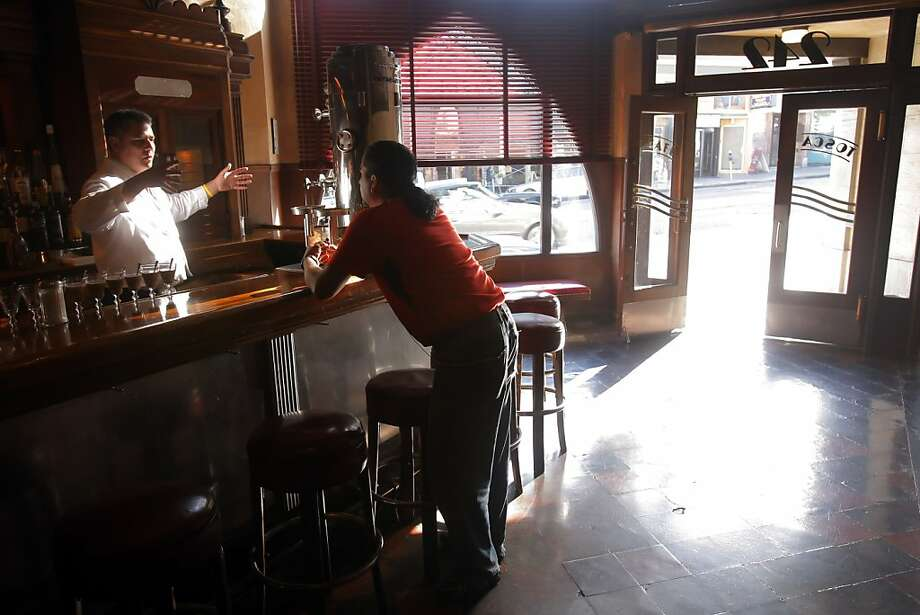 Celebrities and regulars alike are welcomed at Tosca Cafe. Carlos Hurtado talks to his bartender friend, Ernie Evangelista, at a watering hole frequented by the likes of Francis Ford Coppola. Photo: Carlos Avila Gonzalez, The Chronicle