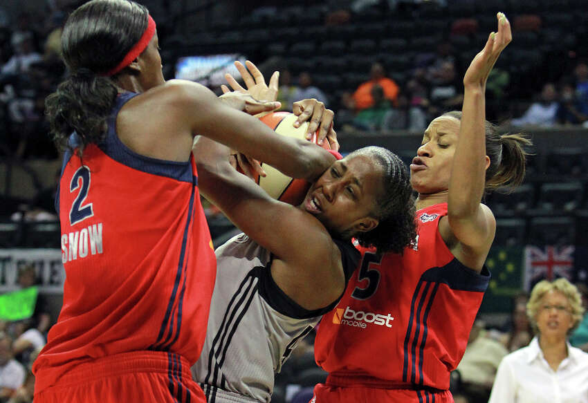 San Antonio 's Shenise Johnson gets tied up in the lane by Michelle Snow and Jasmine Thomas as the Silver Stars host the Washington Mystic at the AT&T Center on August 21, 2012.