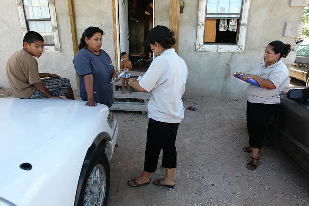 "Promotoras Elida Perez (center) and Linda Medrano (right) chat with Sonia Garcia (second from left) at her home in the North San Carlos colonia in Edinburg, Texas. The area has seen a dramatic increase in the amount of recipients receiving food benefits via the Lone Star Card - a debit card issued by the Texas Health and Human Services Commission. One of the reasons for the rise is in part due to the efforts of the organization, Migrant Health Promotion, and their ""promotoras"" - individuals who work with many families in border communities like Edinburg. The promotoras help the families - many of whom the adults are undocumented but their children are U.S. citizens - to get proper healthcare for the children and to get aid so that the families can afford food in their homes. Photo: Kin Man Hui, San Antonio Express-News / ©2012 San Antonio Express-News"