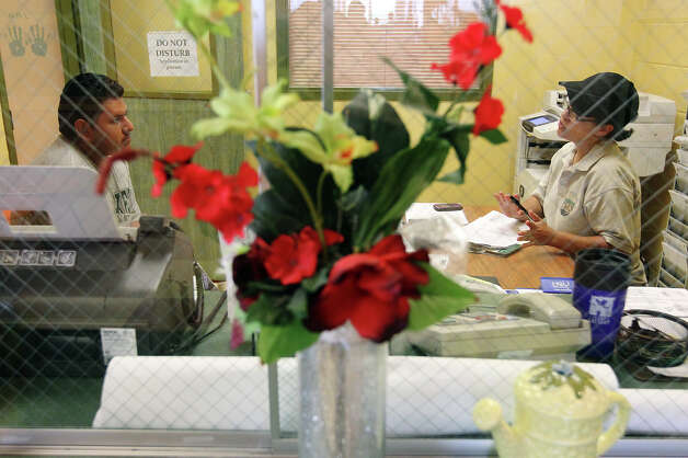 "Promotora Elida Perez (right) helps with filling out an application for medical aid at the San Carlos Community Resource Center in Edinburg, Texas on Wednesday, July 25, 2012. The area of Edinburg, Texas has seen a dramatic increase in the amount of recipients receiving food benefits via the Lone Star Card - a debit card issued by the Texas Health and Human Services Commission. One of the reasons for the rise is in part due to the efforts of the organization, Migrant Health Promotion, and their ""promotoras"" - individuals who work with many families in border communities like Edinburg. The promotoras help the families - many of whom the adults are undocumented but their children are U.S. citizens - to get proper healthcare for the children and to get aid so that the families can afford food in their homes. Photo: Kin Man Hui, San Antonio Express-News / ©2012 San Antonio Express-News"