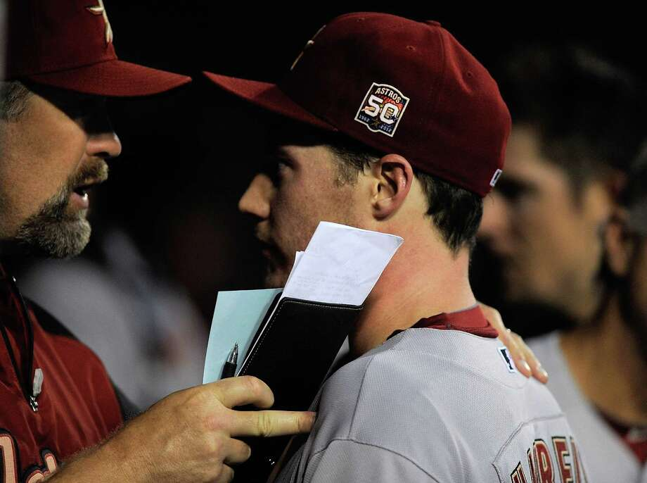 The learning curve is steep for Lucas Harrell, right, Tuesday as his rare rough outing necessitates a visit from pitching coach Doug Brocail between innings. Photo: Jeff Curry / 2012 Getty Images