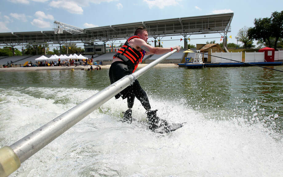 Jason Rzepa cruises by the stadium on a ski run as volunteers help with All Can Ski, a waterskiing clinic for people with disabilities, at SeaWorld on August 21, 2012.  Rzepa lost his lower legs when an IED detonated in Iraq in 2011.  (He emphasizes that it happened in Iraq.)   August 21, 2012. Photo: Tom Reel, San Antonio Express-News / ©2012 San Antono Express-News