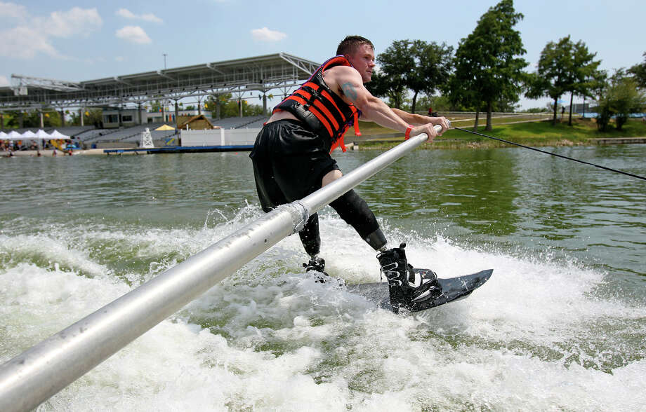 Jason Rzepa cruises by the stadium on a ski run as volunteers help with All Can Ski, a waterskiing clinic for people with disabilities, at SeaWorld on August 21, 2012.  Rzepa lost his lower legs when an IED detonated in Iraq in 2011.  (He emphasizes that it happened in Iraq.) Photo: Tom Reel, San Antonio Express-News / ©2012 San Antono Express-News