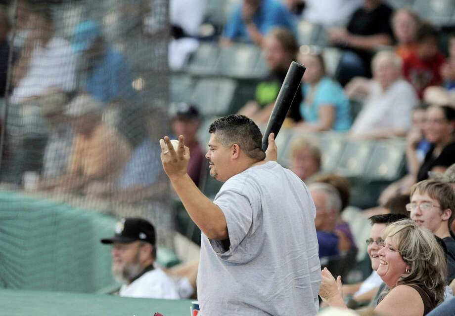 A fan shows off the baseball bat he caught after it flew out of a batter's hand and into the crowd during a Texas League baseball game between the Frisco Roughriders and the San Antonio Missions, Tuesday, Aug. 21, 2012, in San Antonio. Photo: Darren Abate, Express-News
