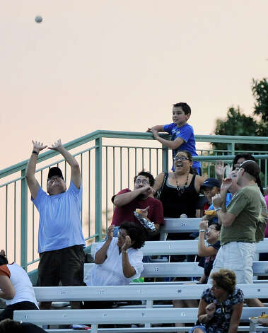 A fan tries to catch a foul ball during a Texas League baseball game between the Frisco Roughriders and the San Antonio Missions, Tuesday, Aug. 21, 2012, in San Antonio. Photo: Darren Abate, Express-News