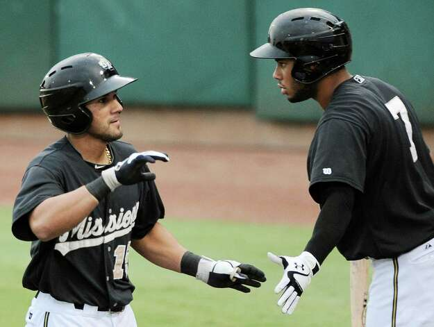 San Antonio Missions' Reymond Fuentes, left, celebrates a run with teammate Jonathan Galvez during a Texas League baseball game against the Frisco Roughriders, Tuesday, Aug. 21, 2012, in San Antonio. Photo: Darren Abate, Express-News