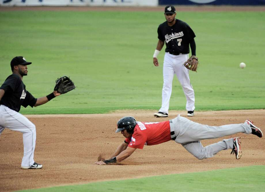Frisco Roughriders' Guilder Rodriguez, right, slides under San Antonio Missions' Jeudy Valdez, left, at second base as Missions' Jonathan Galvez looks on during a Texas League baseball game, Tuesday, Aug. 21, 2012, in San Antonio. Photo: Darren Abate, Express-News