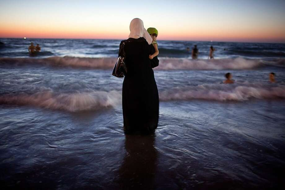 A woman holds her baby as Palestinians enjoy a day at a beach during Eid al-Fitr, which marks the end of the holy month of Ramadan on August 21, 2012 in Tel Aviv, Israel. According to the Israel's coordinator for government activities in the territories, Israel has allowed the entry of over 1 million Palestinians from the occupied West Bank since the beginning of Ramadan due to improved security. Photo: Uriel Sinai, Getty Images