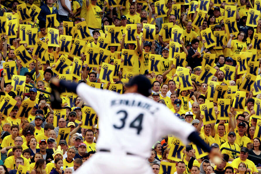 Fans stand to cheer as Seattle Mariners starting pitcher Felix Hernandez throws against the Clevelan