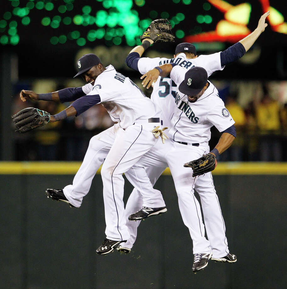 Seattle Mariners outfielders Trayvon Robinson, left, Michael Saunders and Eric Thames celebrate after the team beat the Cleveland Indians in a baseball game Tuesday, Aug. 21, 2012, in Seattle. The Mariners won 5-1. Photo: Elaine Thompson / Associated Press