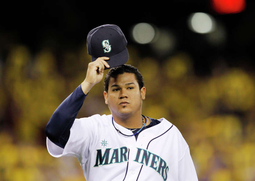 Seattle Mariners starting pitcher Felix Hernandez waves his cap to fans as he leaves the baseball ga