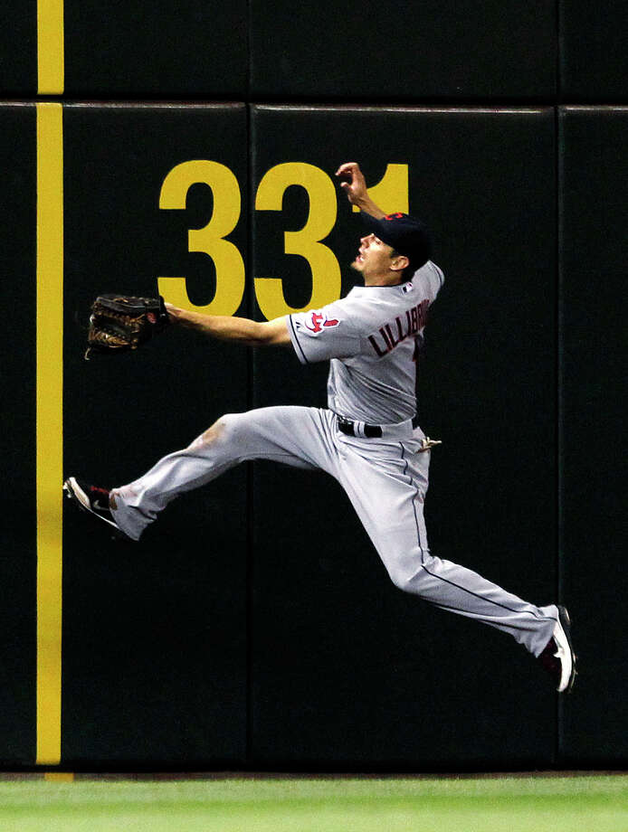 Cleveland Indians left fielder Brent Lillibridge leaps for a fly ball from Seattle Mariners' Michael Saunders in the eighth inning of a baseball game Tuesday, Aug. 21, 2012, in Seattle.  Lillibridge made the catch. The Mariners won 5-1. Photo: Elaine Thompson / Associated Press