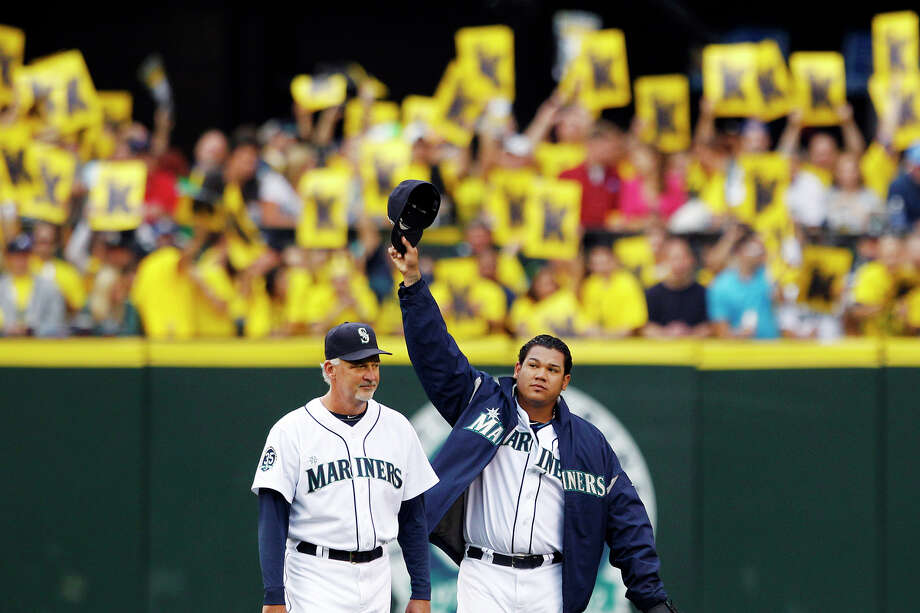 Seattle Mariners starting pitcher Felix Hernandez, right, waves to fans as pitching coach Carl Willis watches Hernandez head onto the field to take his first start in a baseball game since throwing a perfect game six days earlier, Tuesday, Aug. 21, 2012, in Seattle. Hernandez and the Mariners faced the Cleveland Indians. Photo: Elaine Thompson / Associated Press