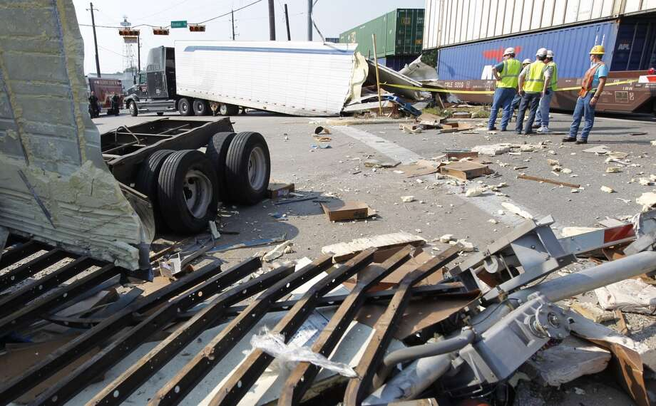 Harris County deputies respond to an accident where the driver of an 18-wheeler didn't completely cross over the railroad tracks while traveling east on Rankin Road.  The train struck the end of trailer, splitting it in half and slamming into two vehicles waiting on a red light along East Hardy Road on Aug. 22, 2012. ( Mayra Beltran / Houston Chronicle )