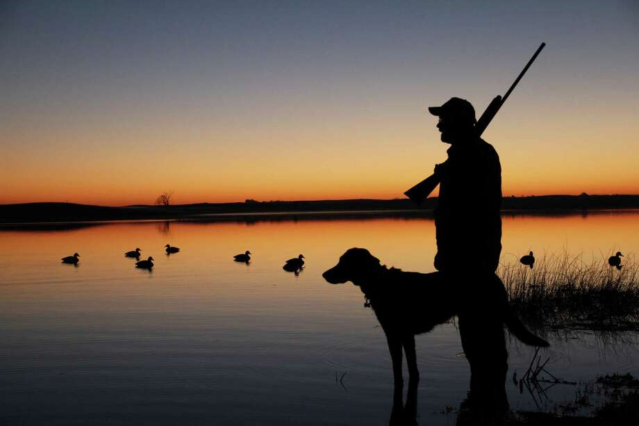MAGIC IN THE AIR -  A veteran waterfowler and his dog drink in the rich sights, sounds, scents and  sense of wonder and anticipation  that, in some, fuel a life-long passion tied to pursuit of ducks and geese. (Chronicle photo by Shannon Tompkins) Photo: Shannon Tompkins / Houston Chronicle