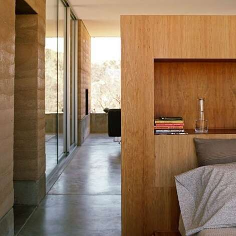 Double duty: Tucson architect Rick Joy is known for clean, simple designs, and his rammedearth house is no exception. Its  bedroom  is separated from the rest of the house only by a half-wall that also acts as a headboard. A rectangular recess on the wall