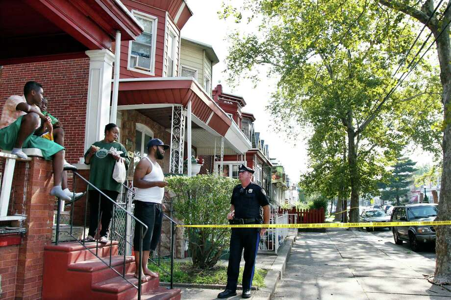 """A police officer talks to neighbors near 1415 Kaighn Ave., in Camden, N.J., Wednesday, Aug. 22, 2012,  Police say a New Jersey mother apparently decapitated her 2-year-old boy and put his head in the freezer of their home before she fatally stabbed herself. Chevonne Thomas, 33, called 911 just after midnight to say something had happened to her child and it """"sounded like she had done it,"""" said Jason Laughlin, a spokesman for the county prosecutor's office. Officers found Zahree Thomas' body on the first floor of the Camden home and the boy's head in the freezer. The mother stabbed herself in the neck with a kitchen knife and died, Laughlin said. (Photo/Mel Evans) Photo: Mel Evans, STF / AP"""