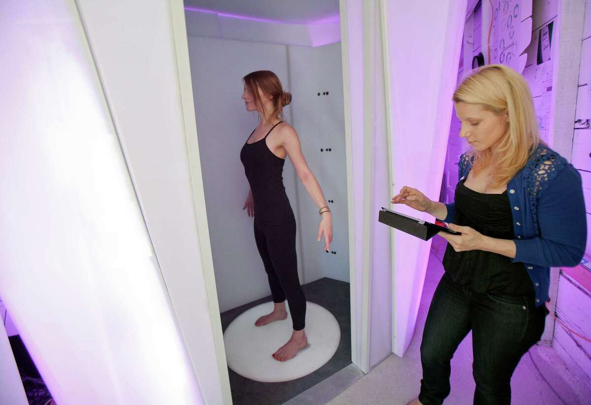 At left, model Jaela Judd uses the Bodymetrics scanning system as Bodymetrics Creative Director Tania Fauvel controls the scan and monitors the results on an iPad at a demonstration in Palo Alto, California, on August 3, 2012. (LiPo Ching/San Jose Mercury News/MCT)