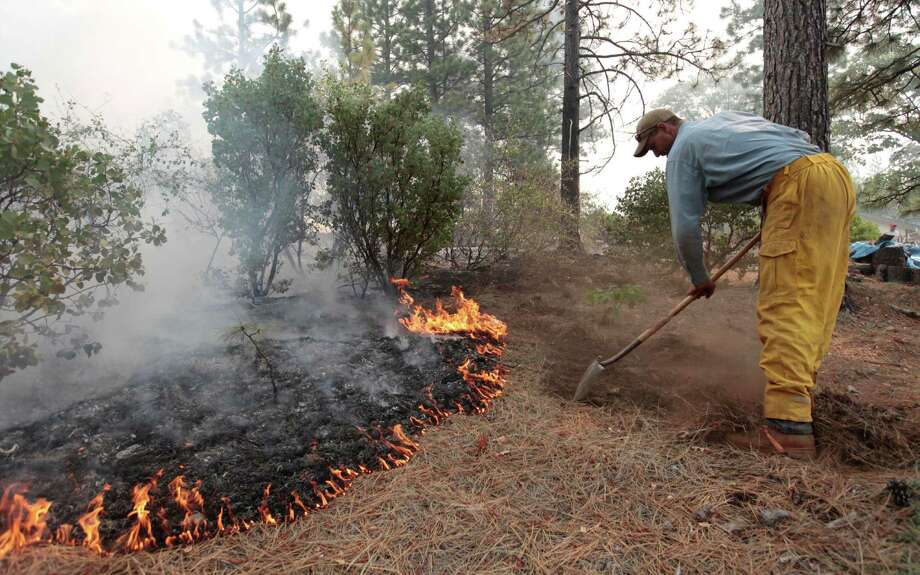 Greg McCarty builds a fire line as flames from the Ponderosa Fire approach the home of a family friend, near Paynes Creek  Calif., Wednesday, Aug. 22, 2012.   The Ponderosa Fire has destroyed 50 structures and burned more than 24,000 acres and is at  50 percent containment(AP Photo/Rich Pedroncelli) Photo: Rich Pedroncelli, Associated Press / AP