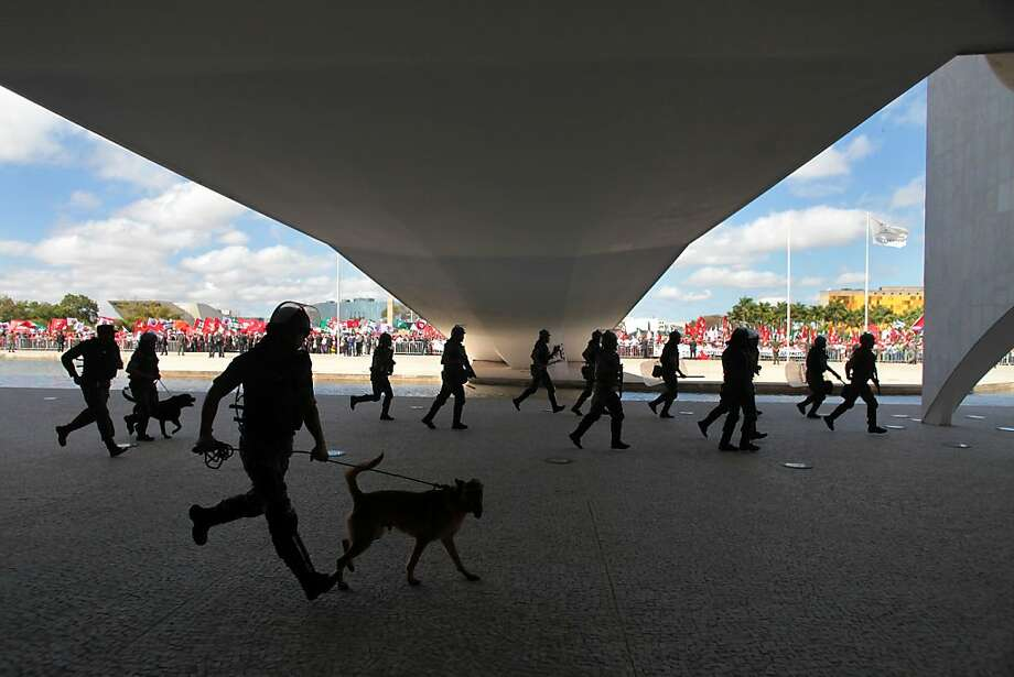Army military police rush to stand guard as rural workers participating in a protest march arrive at the Planalto presidential palace, in Brasilia, Brazil, Wednesday, Aug. 22, 2012. According to officials more than 5,000 representatives of rural social movements marched to the presidential palace demanding the government resolve the country's agrarian issues including the demarcation of indigenous lands and financing for small family farms.  Photo: Eraldo Peres, Associated Press