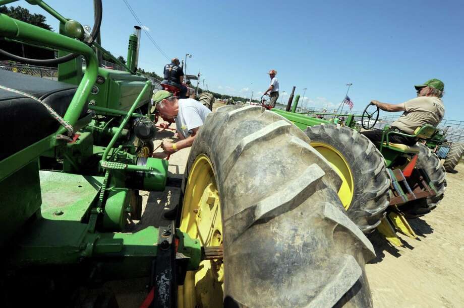 Robert Bronk , left,of Meco,NY readies his tractor for the stone bolt pull during the Washington County Fair in Greenwich, NY Wednesday Aug. 22, 2012. (Michael P. Farrell/Times Union) Photo: Michael P. Farrell