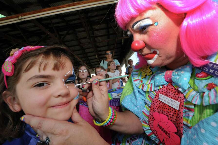 Six-year-old Erica Siaulnski of Argyle, left, gets her face painted by Puddles The Clown during the