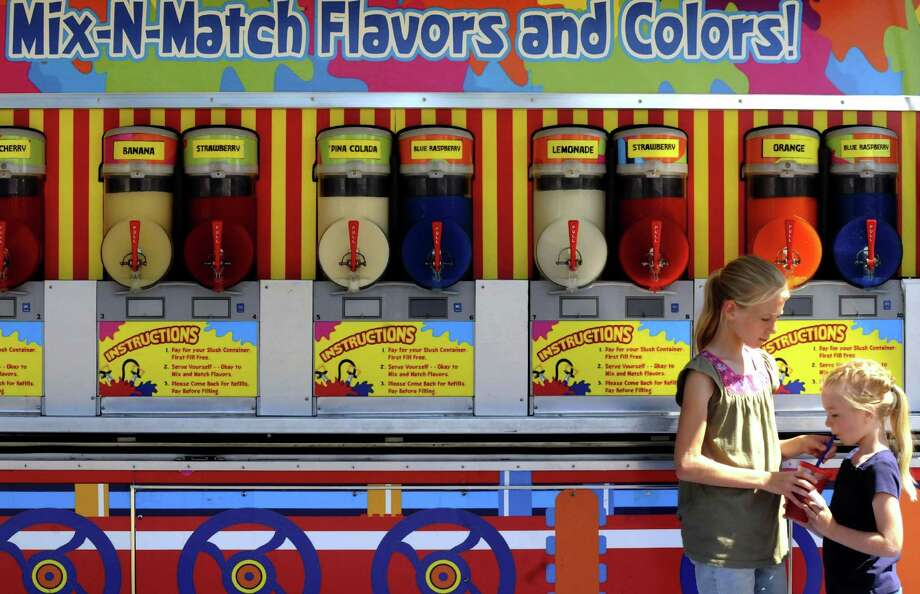 Eleven-year-old Samantha Neigh shares some of her mixed slushy drink with her sister Abigail Neigh during the Washington County Fair in Greenwich, NY Wednesday Aug. 22, 2012. (Michael P. Farrell/Times Union) Photo: Michael P. Farrell