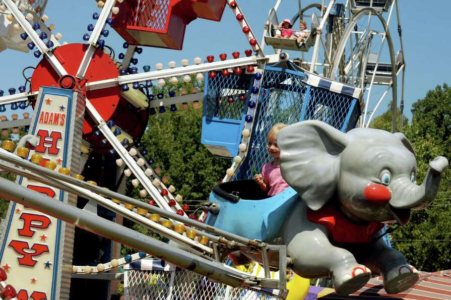 Three-year-old Carly Sherwood enjoys her time on the Flying Elephant ride during the Washington Coun