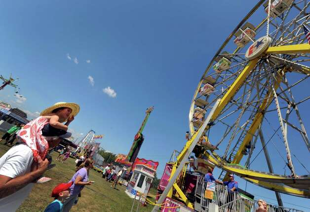 Three-year-old Alexandra Porter, left, rides on her grandfather Dave Perkins sholders as they tour the midway at the Washington County Fair in Greenwich, NY Wednesday Aug. 22, 2012. (Michael P. Farrell/Times Union) Photo: Michael P. Farrell